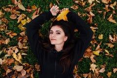 Женщина фитнеса принимает остатки на парк падения Окруженный листьями осени на зеленой лужайке Стоковые Изображения