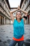 Женщина фитнеса при наушники делая йогу outdoors Флоренция Стоковые Фотографии RF