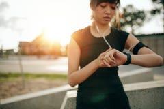 Женщина фитнеса проверяя ее представление на smartwatch Стоковое Изображение