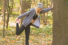 Женщина фитнеса протягивая ее мышцы перед тренировкой, подготавливает для jogging в передних частях Стоковые Фотографии RF