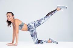Женщина фитнеса протягивая ноги на поле Стоковая Фотография RF