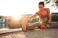 Женщина фитнеса протягивая перед бегом