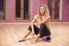 Женщина фитнеса сидя на циновке крытой стоковые фотографии rf
