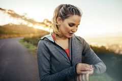 Женщина фитнеса смотря ее наручные часы стоковое изображение rf