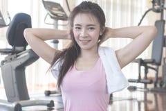 Женщина фитнеса с полотенцем перед зеркалом в fitn стоковая фотография rf