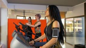 Женщина фитнеса с ремнем руки smartphone слушая к музыке и делая деятельность при спорта видеоматериал