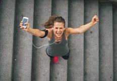 Женщина фитнеса с сотовым телефоном outdoors в городе Стоковое фото RF