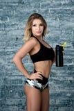 Женщина фитнеса усмехаясь с счастливой свежей энергией пока потеть и питьевая вода от бутылки Стоковые Фотографии RF