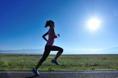 Женщина фитнеса sporty бежать на проселочной дороге Стоковое Изображение