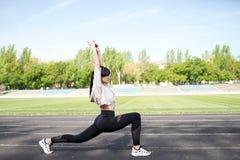 Женщина фитнеса sporty во время на открытом воздухе разминки тренировок r o o Sporty здоровая женщина стоковые фото