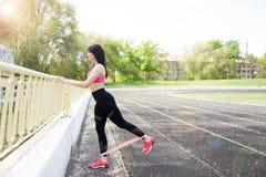 Женщина фитнеса sporty во время на открытом воздухе разминки тренировок r o o Sporty здоровая женщина стоковое фото