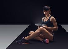 Женщина фитнеса sporty используя цифровую таблетку стоковая фотография rf