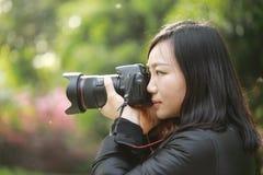 Женщина фотографа перемещения природы держа парк камеры весной Стоковые Фото