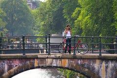 Женщина фотографирует стоя на мосте в Амстердаме. Стоковое Изображение RF