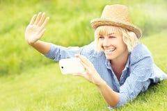 Женщина фотографируя на траве Стоковое фото RF
