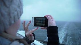 Женщина фотографируя холодное море от шлюпки видеоматериал
