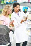 Женщина химика фармации советуя с в аптеке Стоковая Фотография