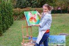 Женщина художника держит картину и смотрит ее, представляющ на камере стоковое изображение