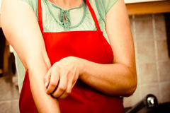 Женщина царапая зудящую руку аллергически стоковая фотография