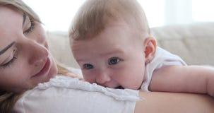 Женщина целуя ее дочь младенца дома сток-видео
