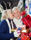 Женщина целуя счастливого человека с подарками на рождество Стоковые Изображения RF