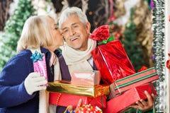 Женщина целуя человека держа подарки на рождество Стоковые Изображения