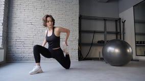 Женщина циновки йоги молодая атлетическая протягивая бедро, мышцы подколенного сухожилия, мышцы ноги внутри помещения в спортзале сток-видео
