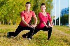 Женщина человека и женщины делая йогу в парке Стоковая Фотография