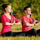 Женщина человека и женщины делая йогу в парке Стоковые Фото