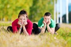 Женщина человека и женщины делая йогу в парке Стоковая Фотография RF