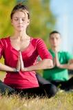 Женщина человека и женщины делая йогу в парке Стоковые Изображения RF