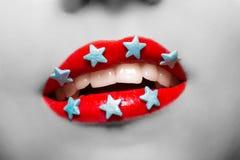 Женщина черно-белого портрета усмехаясь с губами покрасила красные звезды губной помады и конфеты стоковое фото rf