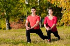 Женщина человека и женщины делая йогу в парке Стоковое Изображение