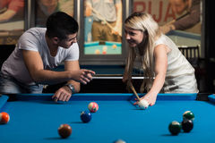 Женщина человека уча как сыграть бассейн Стоковые Фотографии RF