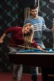 Женщина человека уча как сыграть бассейн Стоковое фото RF