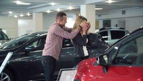 Женщина человека удивительно с новым автомобилем в комнате выставки акции видеоматериалы