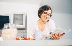 Женщина читает кассету и выпивает чай утра на кухне Стоковое Фото
