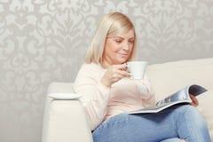 Женщина читает кассету дома Стоковая Фотография RF
