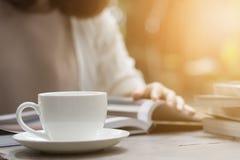 Женщина читает книгу и выпивая кофе стоковая фотография rf