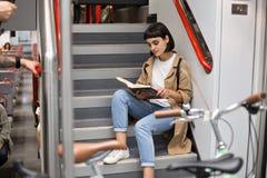 Женщина читает книгу на лестницах поезда стоковые изображения rf
