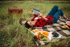 Женщина читает книгу, пикник на луге стоковые фотографии rf