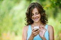 Женщина читает сообщение к мобильному телефону Стоковые Изображения