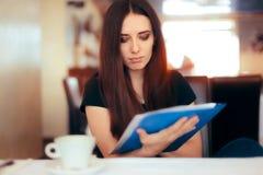 Женщина читая важные документы в ресторане Стоковое Фото