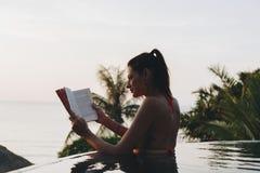 Женщина читая книгу в бассейне стоковое изображение