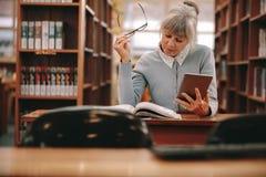 Женщина читая книгу в библиотеке стоковое изображение
