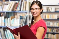Женщина читая книгу в библиотеке стоковая фотография