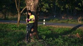 Женщина читая книгу в саде сток-видео