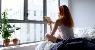 Женщина читая книгу в спальне дома 4k сток-видео