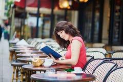 Женщина читая книгу в традиционном парижском внешнем кафе, Париже, Франции Стоковое Изображение RF