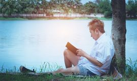 Женщина читая книгу наслаждается руки женщины остатков держа книгу Стоковые Изображения